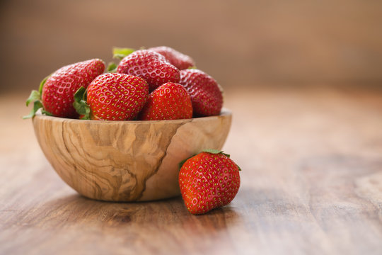 fresh ripe strawberries in wood bowl on table