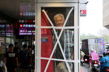 An advertisement display window is taped on a street in Taipei