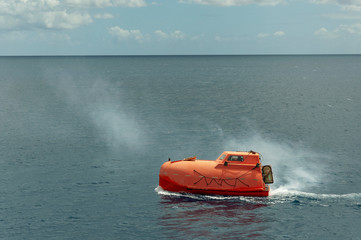 Free-fall life boat being tested at sea.
