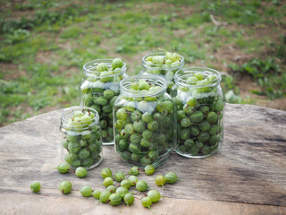 Green gooseberry berries in jars on the table
