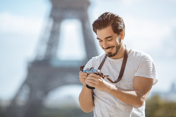 Fototapeta Paris Eiffel Tower tourist with camera taking pictures in front of the Eiffel tower, Paris, France. Young professional photographer handsome man in casual clothes outdoors in Europe. obraz