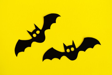 Holiday decorations for Halloween. Two black paper bats on a yellow background, top view.