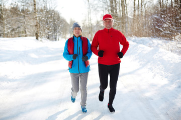 Active seniors jogging down winter road in the forest on sunny day or morning