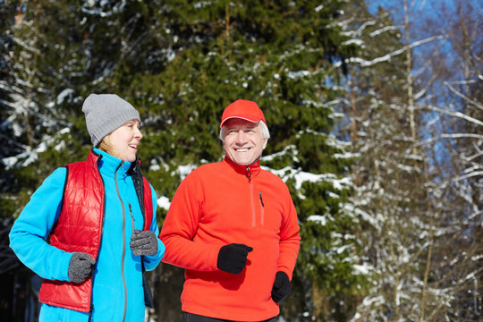 Active mature spouses in sportswear running in winter forest and talking