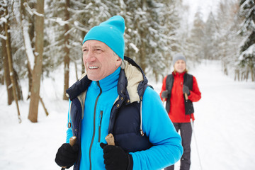 Mature man in blue activewear looking forwards while searching for place for skiing practice