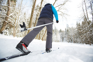 Rear view of sportsman in activewear moving on skis in snowdrift in winter forest