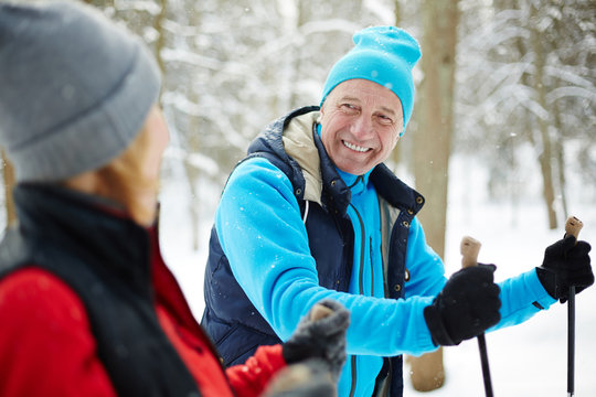 Happy mature man in activewear looking at his wife while skiing in winter forest at leisure