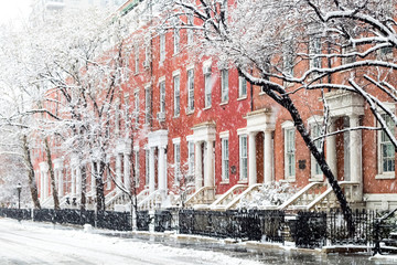 Snowy winter street scene with historic buildings along Washington Square Park in Manhattan, New York City