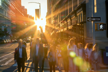Fotomurales - Crowd of blurred people crossing a busy intersection on 5 th Avenue in New York City with the bright light of sunset in the background