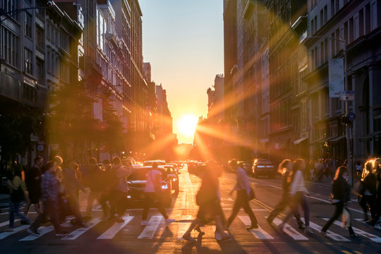 Sunlight shines over the buildings and people of a busy Midtown Manhattan street scene in New York City
