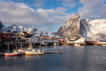 Scenic view of the small norwegian fishing village Hamnoy. Beautiful winter daytime landscape with boats, fjord, peaks of rocky mountains and blue cloudy sky on background, Lofoten Islands, Norway