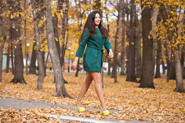 Portrait of a young beautiful brunette woman in short green coat