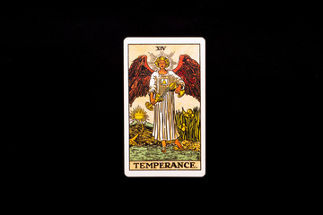 An individual major arcana tarot card isolated on black background. Temperance.