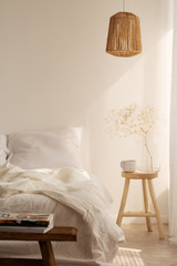 Bedside table with mug and flower next to bed with white bedding, pillow and blanket, real photo with copy space on the empty wall