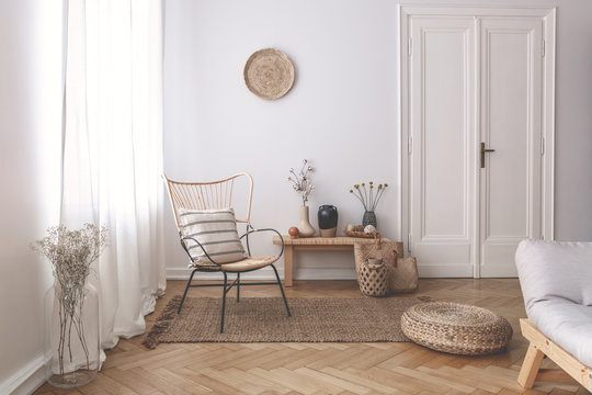 Sheer white curtains on the window of a white living room interior with a striped, linen pillow on a modern wicker chair