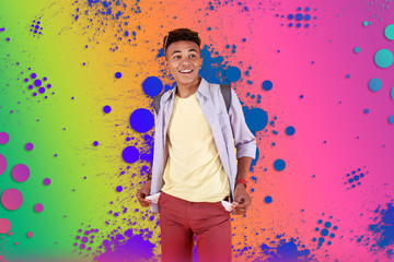 Empty pockets. Stylish mulatto teenager wearing dark red shorts showing his empty pockets while standing in front of colorful background