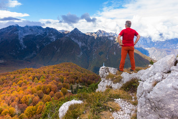 Senior hiker standing on top and admiring the mountains landscape with forest in autumn colors