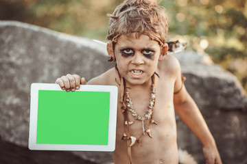 Caveman, manly boy holding tablet PC with green screen. Funny young primitive boy outdoors. Evolution degradation concept. Calm boy outside against rocky background. Prehistoric tribal man outside on