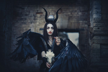 Pretty demon girl with black wings behind her back, goddess of another world beyond, Halloween black angel