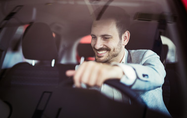 Attractive happy young man driving car and smiling Wall mural