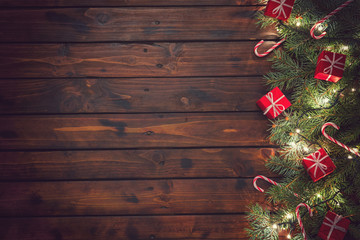 Christmas background with ornaments and gift boxes on the old wooden board