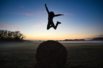 Happy woman jumping for joy on the background of the field and the setting sun.