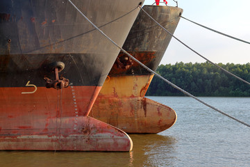 Türaufkleber Schiff Prows of two old rusty ships with anchor chain anchored at Danube river at summer