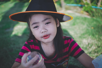 little girl in witch dress at backyard.