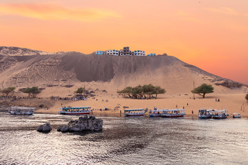 In the way to the Nubian village at sunset, with a village in the dune of the desert Aswan, Egypt
