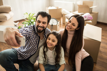 Attractive guy is taking selfie with his wife and kid. All of them are smiling and looking to the camera. There are some boxes behind them that needs to be unpacked.