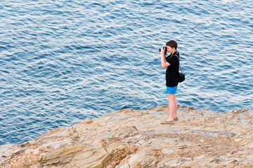 young man photographs the sea