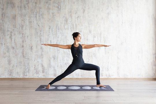 Slender asian girl standing in yoga asana against concrete wall
