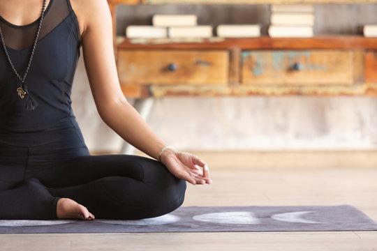 Slender asian yoga girl sitting in Lotus pose close up