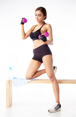 The lady is wearing exercise suit,hold dumbbell in hand and raise up,for built muscle