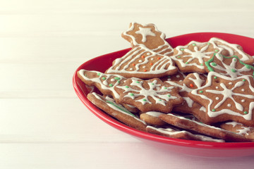 festive dessert for Christmas/ red plate full of different shaped cookies on the table front view