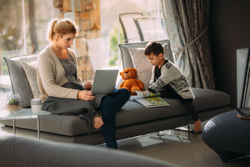 Mother working on laptop and son reading story book