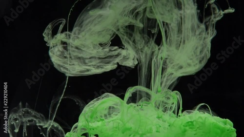 Closeup green ink being poured into water over black