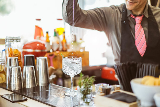 Bartender mixing a cocktail in a crystal glass in an american bar - Barman pouring alcohol in a glass with aromatic herbs - Profession, lifestyle, drink concept