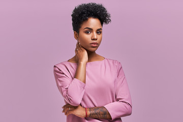 Gorgeous dark skinned young female with Afro hairstyle and confident look, poses for fashionable magazine, looks aside thoughtfully, wears trendy shades, poses against lavender studio background