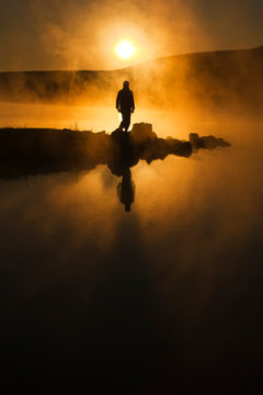 A warm, foggy sunrise silhouettes a hiker against a cold early morning mist across a lake. The mist hung perfectly still in completely calm air almost as a spirit greeting the new day.
