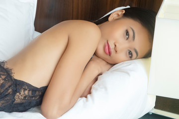 Asian woman wearing black lingerie on bed with white sheets