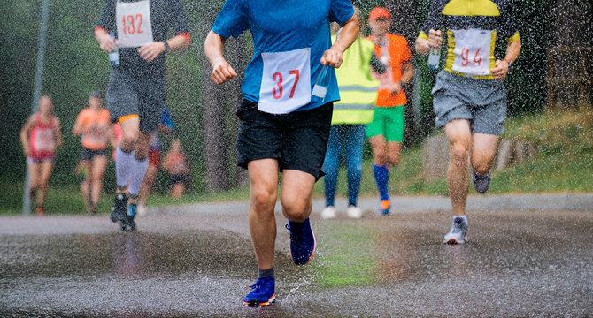 runners running under rain drops city marathon