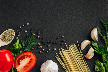Spaghetti and pasta ingredients on a dark background, top view