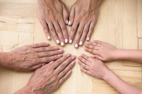 Top view of hands of three generations of women put in circle show unity and support, mother, daughter and grandmother palms together on surface demonstrate eternal love and care. Family value concept