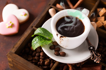 Close up cup of coffee on a wooden box with grains of coffee and mint
