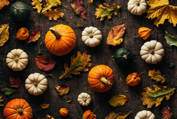 Colourful autumn leaves and pumpkin over old background. Autumn background. Top view.