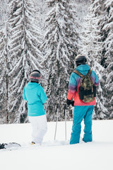 Happy Skier and snowboarder friends standing on mountain top with and snowboard in hands. back view