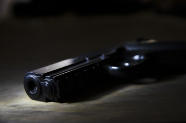 Black Gun on a wooden surface close-up. Studio shot. Top view