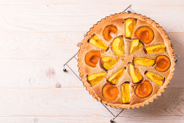 Open pie with peaches in almond cream on a white wooden background. Delicious and sweet peach tart