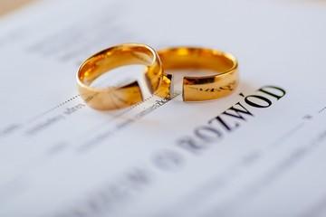 Divorce decree in Polish language and two broken wedding rings